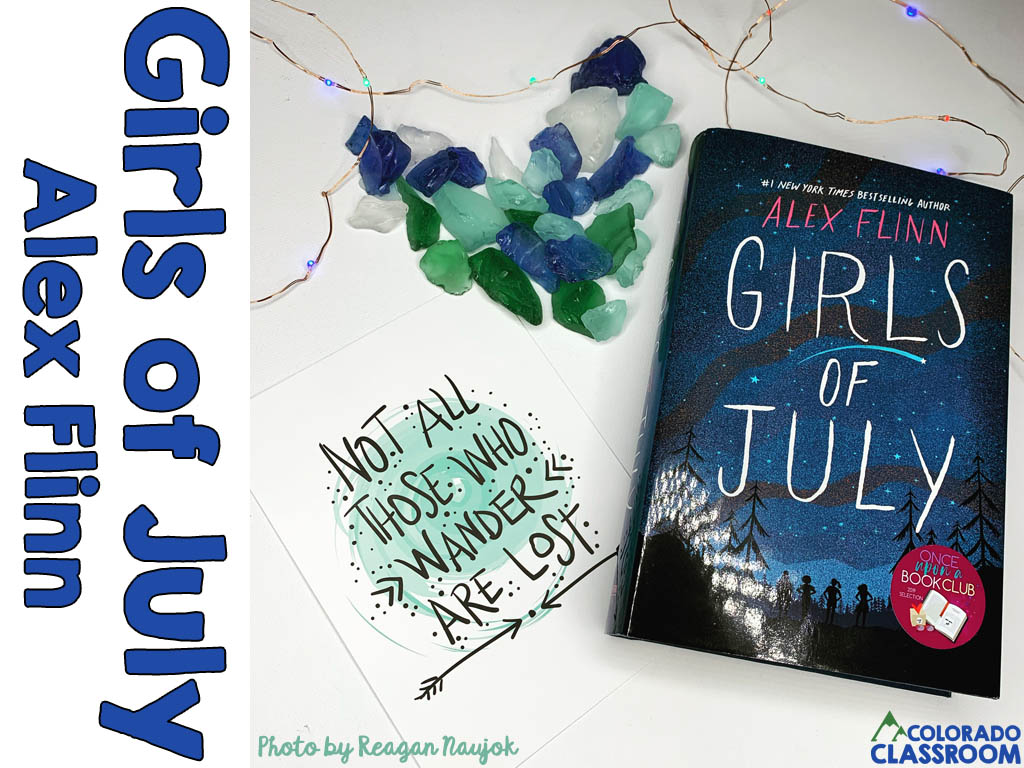 A book, Girls of July, in a stylized pose with a quote card, a heart made out of blue, green and white rocks, and some twinkling lights.