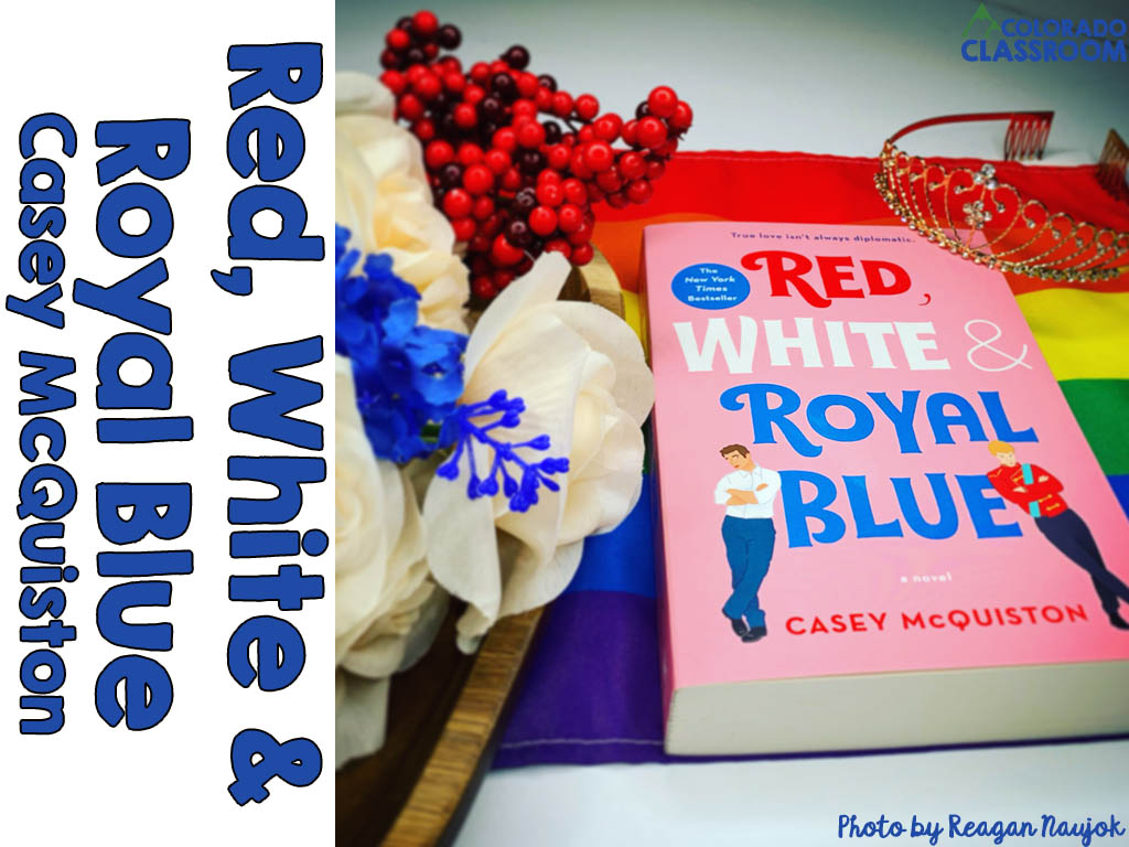 A book, Red White & Royal Blue, in a stylized pose with some white and blue silk flowers, plastic red berries, a wooden tray, a Pride flag, and a tiara.